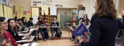 Teacher in classroom with students raising hands