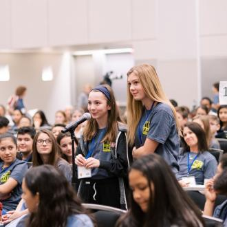 Two students standing in audience