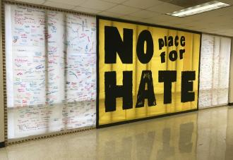 No place for hate sign on wall with signatures