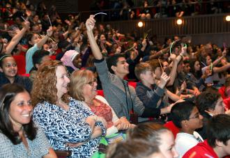 Students raising hands in auditorium